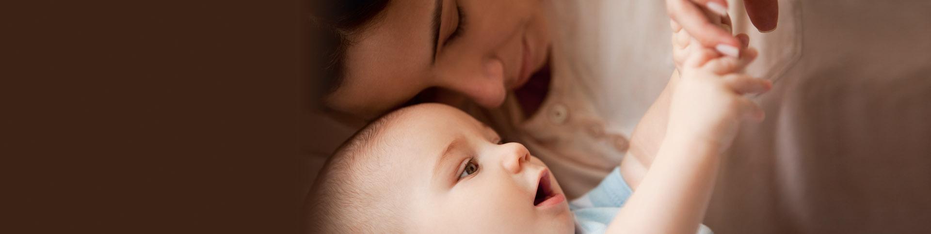 Mujer y bebé en primer plano recostados.